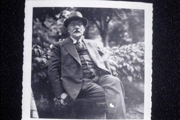 Aron Freimann, seated outdoors.